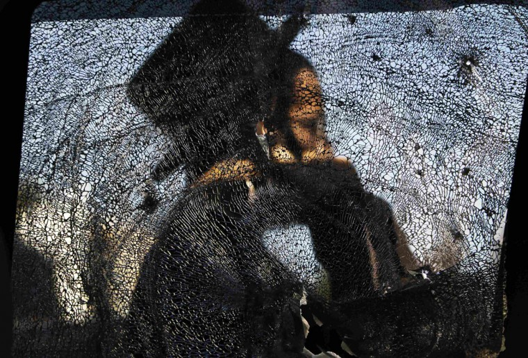 An ultra-Orthodox Jewish man is seen through a damaged car window after a rocket fired from Gaza landed in the southern city of Ashdod. Israel has started drafting 16,000 reserve troops, the military said on Friday, in a sign that violence could escalate further with Palestinian militants in the Gaza Strip. (Amir Cohen/Reuters)
