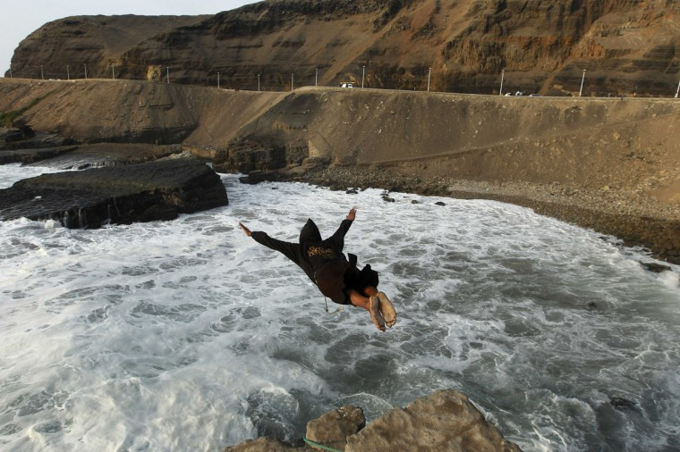 "A man dressed as a friar jumps from a 13-meter high cliff during the ""Jump of the Friar"", along Herradura Beach in Lima. The jump was to commemorate a local legend, that of a friar who leapt into the sea from the same rock to commit suicide over his love of a woman, some two hundred years ago. (Mariana Bazo/Reuters)"
