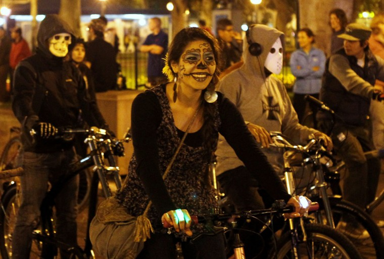 A cyclist with a 'calavera,' or skull, painted on her face participates in a Critical Mass Bike Ride across Lima to celebrate the Day of the Dead, November 1, 2012. Hundreds of cyclists ride through the city to promote cycling as an environmentally friendly mode of transportation. (Mariana Bazo/Reuters)