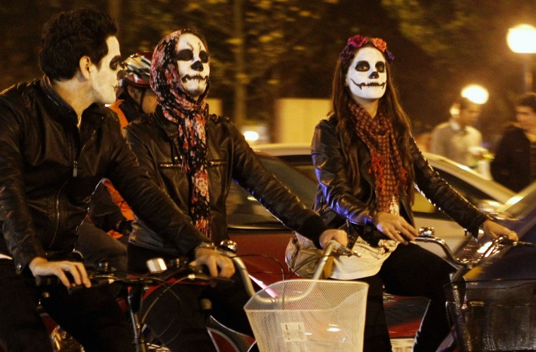 Cyclists with a 'Calavera,' or skull, painted on their faces participate in a Critical Mass Bike Ride across Lima to celebrate the Day of the Dead, November 1, 2012. (Mariana Bazo/Reuters)