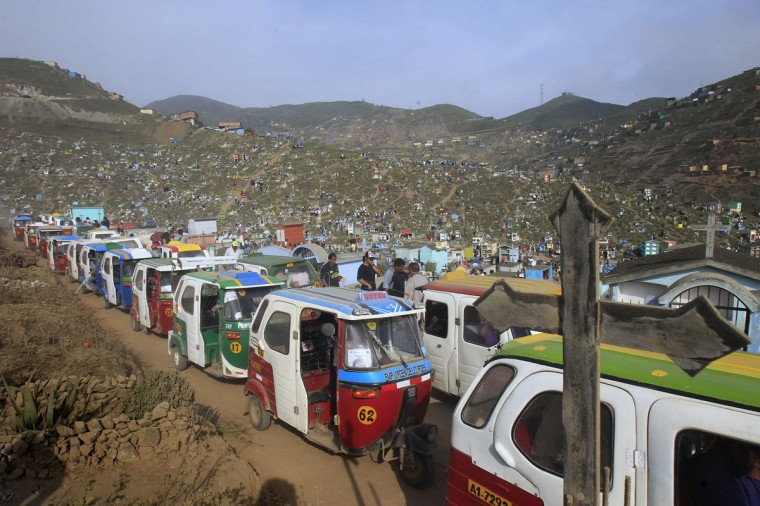Auto rickshaw taxis pass the Nueva Esperanza cemetery during Day of the Dead celebrations in Villa Maria, Lima November 1, 2012. Each year people visit the cemetery, one of Latin America's largest, to honour the dead. (Enrique Castro-Mendivil/Reuters)