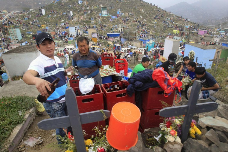 People drink bottles of beer next to the graves at Nueva Esperanza cemetery during Day of the Dead celebrations in Villa Maria, Lima November 1, 2012. (Enrique Castro-Mendivil/Reuters)