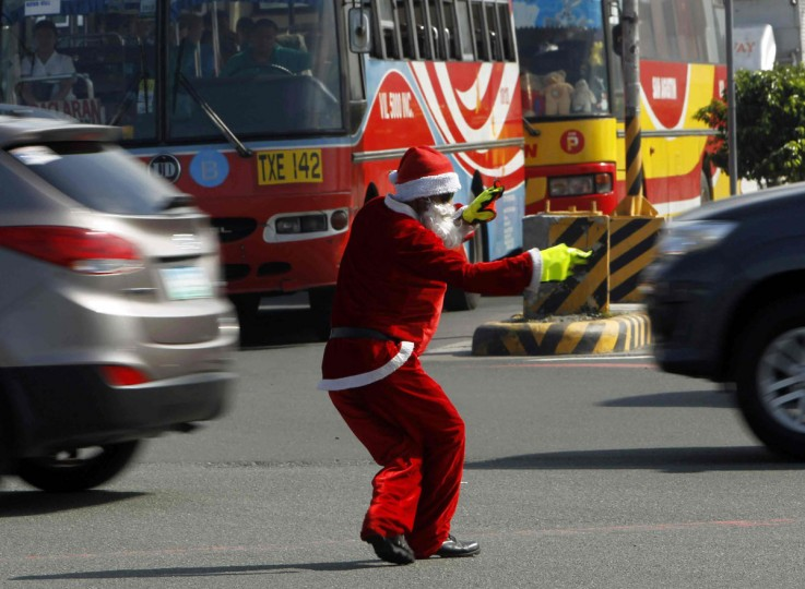 Ramiro Hinojas, 47, a traffic enforcer, wears a Santa Claus costume as he directs traffic along a main street in Pasay city, metro Manila November 22, 2012. Hinojas entertains motorists along Manila's heavily congested main thoroughfare by dressing up as Santa Claus and performing dance moves of pop star Michael Jackson, to mark the upcoming Christmas season. (Romeo Ranoco/Reuters)