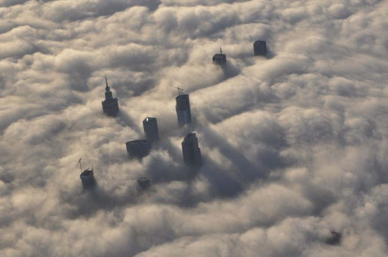 The tops of high rise buildings stick out from a blanket of think fog covering Warsaw early morning. (Mateusz Olszowy/Reuters)