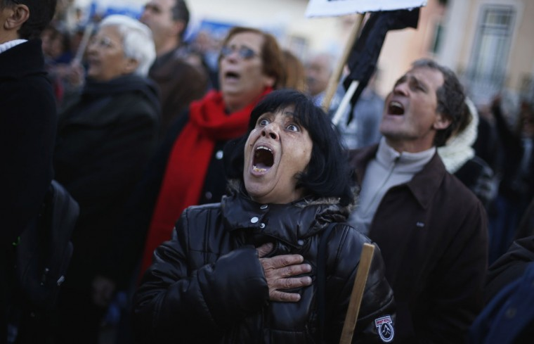 A woman sings the Portuguese national anthem during a protest against austerity, in front of Portugal's parliament in Lisbon. Portugal's parliament gave final approval on Tuesday to a 2013 budget which promises a third year of recession and the biggest tax hikes in modern history to ensure international bailout terms are met. A few thousand protesters gathered outside parliament to oppose the bill, which far-left opposition lawmakers have promised to challenge in the country's constitutional court. (Rafael Marchante/Reuters)