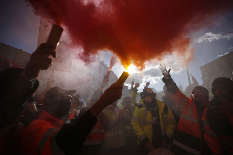 Dockers hold up flares during a protest in front of Portugal's parliament in Lisbon. Hundreds of dockworkers from several European countries joined in a protest in Lisbon on Thursday against plans by the Portuguese government to change labour rules in the sector. Dockworkers from Spain, France, Denmark, Sweden and Belgium were among those from Portugal who marched from a town hall square to the parliament building, where lawmakers were expected to vote in favour of the bill. (Rafael Marchante/Reuters photo)