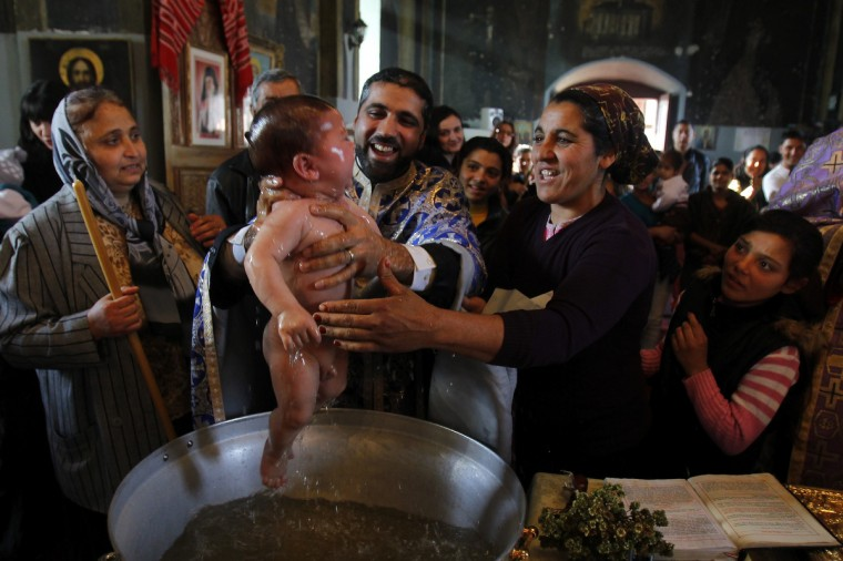 Priest Nicolae Ganga (C), a member of Romania's Roma ethnic minority, baptizes a child during a very rare mass Orthodox baptism ceremony at a church in the Bora neighborhood in Slobozia, 130 km (81 miles) east of Bucharest. About 40 Roma ethnic people, aged between one and 57 years, were baptized into the Orthodox Christian faith with Romanians serving as godparents during a very rare mass ceremony in an attempt to strengthen their community ties with the Romanian majority. The Roma people make up the biggest ethnic minority in the European Union, most of them from countries like Romania, Bulgaria and the Czech Republic. There are an estimated 10 million across Europe and one in five lives in Romania. (Bogdan Cristel/Reuters)