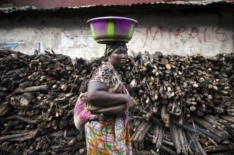 A woman carrying her baby walks past stacked wood near the final campaign rally for Sierra Leone opposition presidential candidate in Freetown November 15,2012. Incumbent President Ernest Bai Koroma, a former insurance executive who came to power in 2007 in elections generally considered free and fair, will face off against former junta leader Bio. Saturday's poll is the latest test of democracy in a region notorious for flawed polls, civil wars, and coups. (Joe Penney/Reuters)