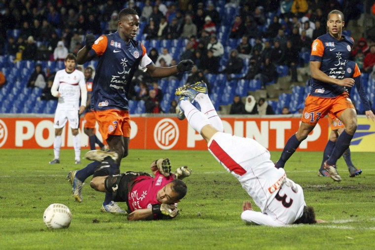 Nice's Alexy Bosetti (R) crashes to the ground after flying over Montpellier's goalkeeper Laurent Pionnier (C) and teammate Mapou Yanga-Mbiwa (L) going for the ball during their French League Cup quarter-final match at the Mosson stadium in Montpellier. (Pascal Parrot/Reuters)