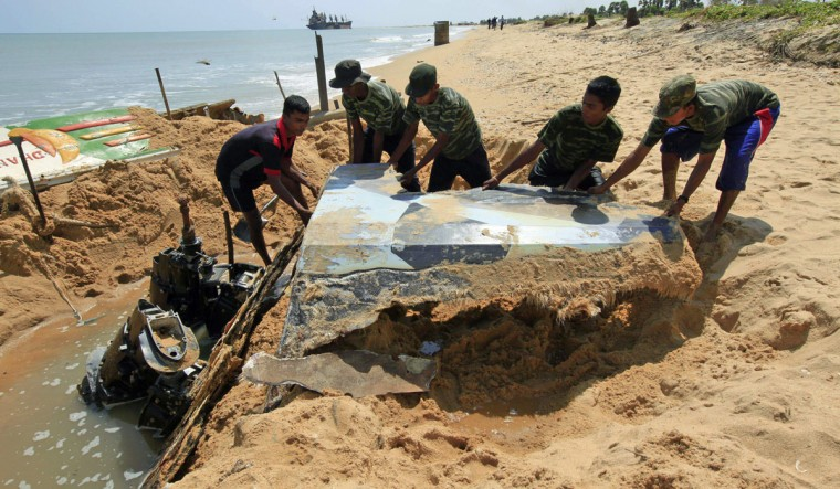 Sri Lankan army soldiers dig out heavy weapons, which they said were buried by the Liberation Tigers of Tamil Eelam (LTTE) at the end of the three-decade war against Sri Lanka troops in 2009, from the sand on Vellamullivaikkal beach in Mullaitivu, northern Sri Lanka. The soldiers recovered four 152mm artillery guns, one 130mm artillery gun and two 120 horsepower engines from the beach. (Stringer/Reuters)