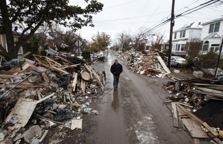 A man walks through piles of debris that have not been removed by the Department of Sanitation outside of homes damaged from flooding that inundated the area during hurricane Sandy in the Queens borough neighborhood of Belle Harbor, New York, November 8, 2012. (Lucas Jackson/Reuters)