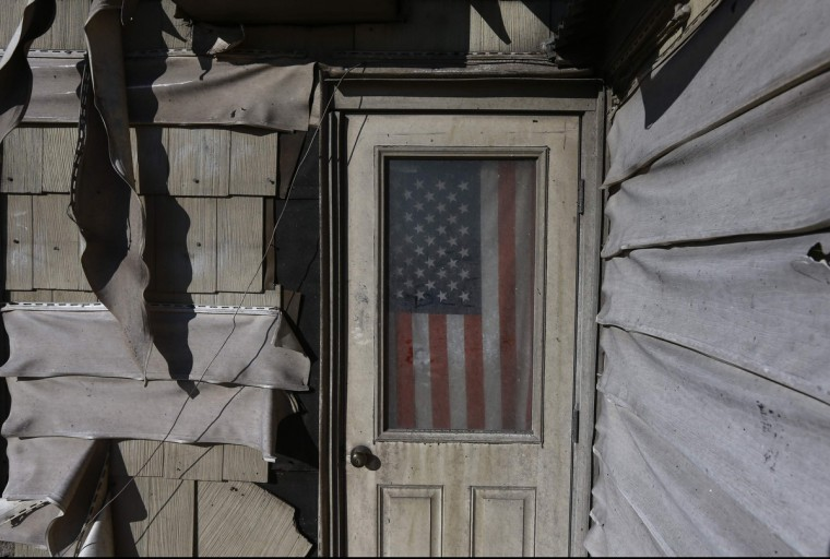 A U.S. flag is seen in the front door of a damaged home in the Breezy Point neighborhood which were left devastated by Hurricane Sandy in the New York borough of Queens. It has become one of the biggest sources of tension between residents and the authorities in the worst-hit areas of New York City after Superstorm Sandy: damaged electrical systems in homes and - making matters worse - not enough electricians to fix them. (Adrees Latif/Reuters)