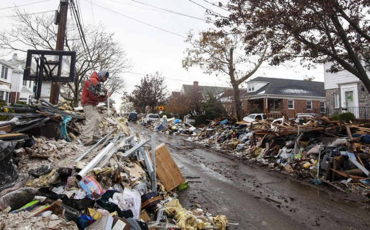 A worker deposits steel onto the top of a pile of debris stacked up outside of homes damaged from flooding that inundated the area during hurricane Sandy in the Queens borough neighborhood of Belle Harbor, New York, November 8, 2012. (Lucas Jackson/Reuters)