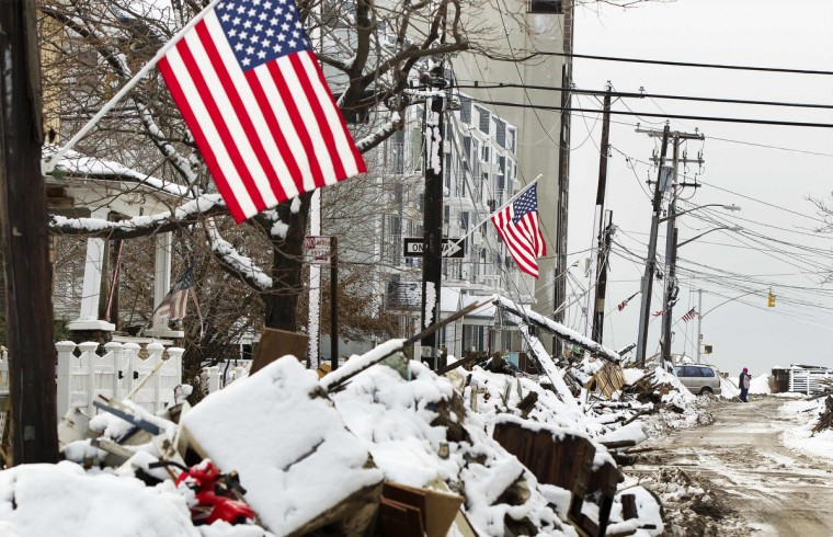 A man stands in the street amongst piles of debris piled up outside of people's homes due to the flooding from hurricane Sandy that are covered in snow left by a nor'easter, also known as a northeaster storm, in the Queens borough neighborhood of Rockaway Beach, New York, November 8, 2012. (Lucas Jackson/Reuters)