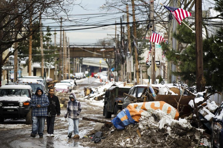 Residents walk down a street past piles of debris piled up outside of people's homes due to the flooding from hurricane Sandy that are covered in snow left by a nor'easter, also known as a northeaster storm, in the Queens borough neighborhood of Rockaway Beach, New York, November 8, 2012. (Lucas Jackson/Reuters)