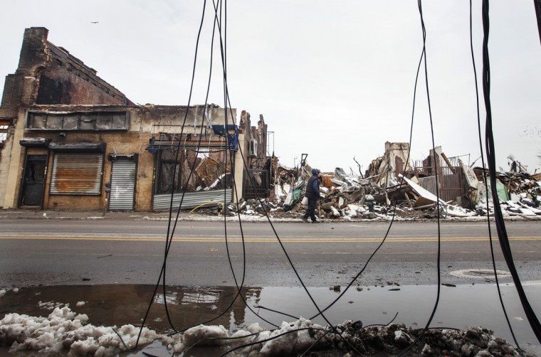 A man walks past buildings destroyed by a fire that took place during hurricane Sandy and through snow left on the ground after a nor'easter, also known as a northeaster storm, in the Queens borough neighborhood of Rockaway Park, New York, November 8, 2012. (Lucas Jackson/Reuters)