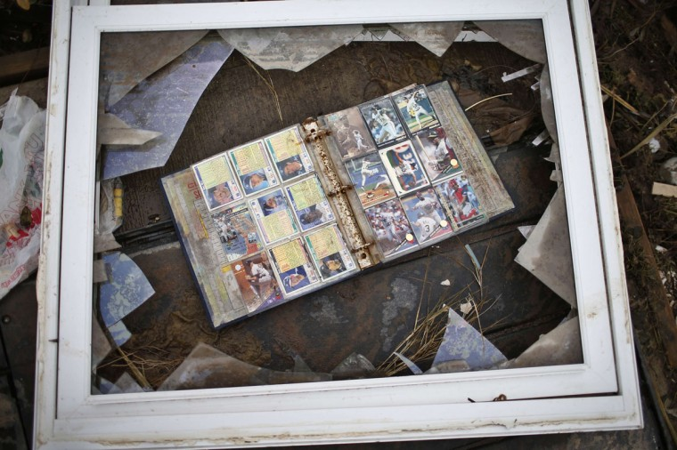 A book of baseball cards lays inside a broken window frame in the remains of a house swept of its foundation by Hurricane Sandy in the Great Kills neighborhood of Staten Island in New York City. (Mike Segar/Reuters)