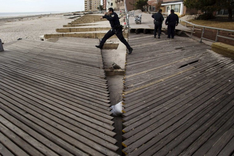 An NYPD officer jumps over a chasm in the boardwalk caused by the storm surge of Hurricane Sandy in the Brooklyn borough region of Belle Harbor in New York. (Lucas Jackson/Reuters)