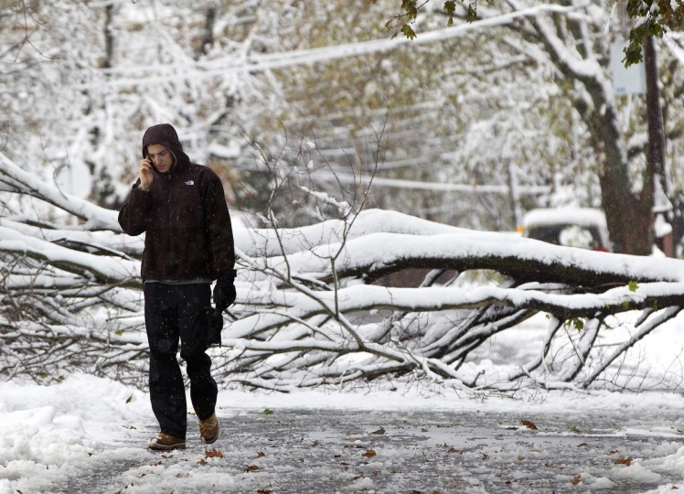 A man walks down a street past a snow covered fallen tree in Roslyn Heights, New York November 8, 2012. An unseasonably early-winter storm brought snow, rain and dangerous winds to the U.S. Northeast, plunging many residents of the most populous region of the country back into darkness just as they were recovering from Superstorm Sandy. (Shannon Stapleton/Reuters)