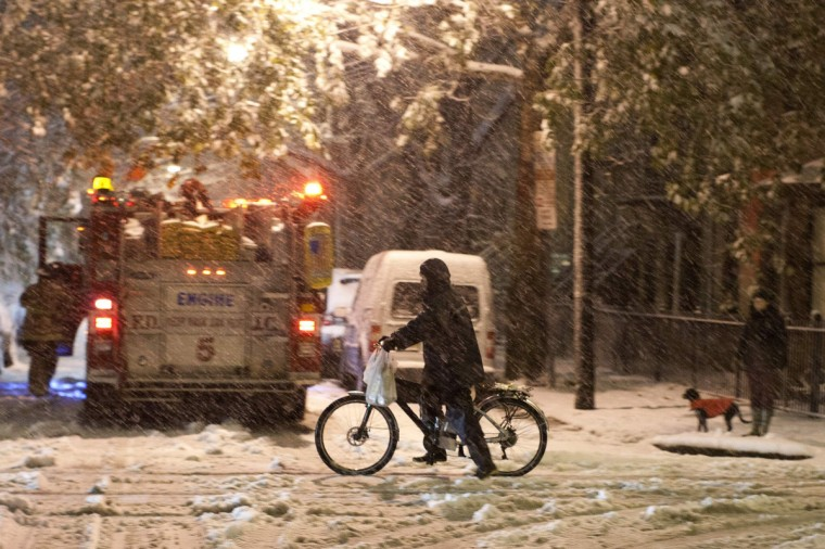 A man rides his bike as a firefighter truck attends to a call as it snows during the nor'easter, also known as a northeaster storm, in Jersey City, New Jersey November 7, 2012. A wintry storm dropped snow and rain on the U.S. Northeast on Wednesday, bringing dangerous winds and knocking out power in a region where hundreds of thousands were still in the dark after Superstorm Sandy. (Eduardo Munoz/Reuters)