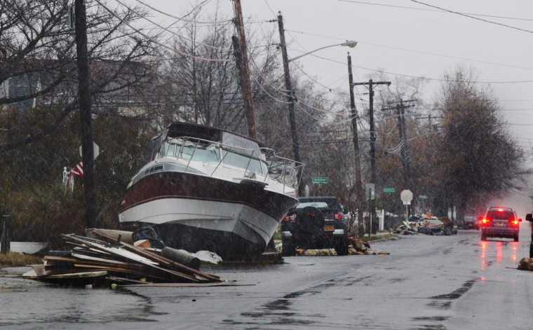 A boat deposited on the street during Hurricane Sandy is seen amid snow fall from nor'easter, also known as a northeaster storm, in Lindenhurst, New York November 7, 2012. The wintery nor'easter storm added misery to thousands of people whose homes were destroyed by superstorm Sandy, which killed 120 people when it smashed ashore on October 29 in the New York-New Jersey area, swallowing entire neighborhoods with rising seawater and blowing homes from their foundations.(Lucas Jackson/Reuters)