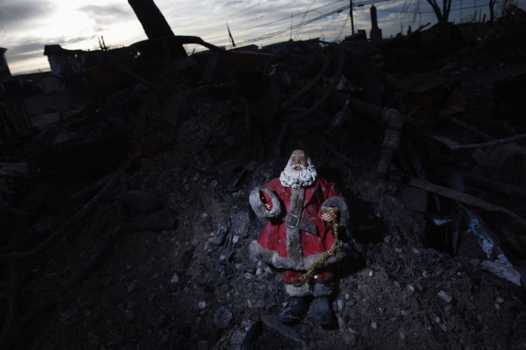 A Santa Claus statue is seen in front of a home destroyed by Storm Sandy in the Breezy Point neighborhood of Queens, New York. (Eric Thayer/Reuters)