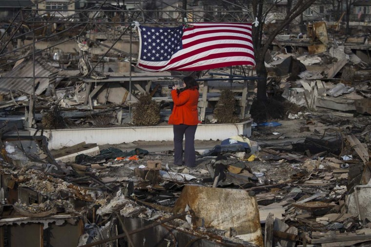 Blythe Finn takes pictures after returning to see her home in Breezy Point, a month after the neighborhood was left devastated by Hurricane Sandy in the New York borough of Queens. The storm killed 132, left thousands homeless and economic damages topping $50 billion. (Adrees Latif/Reuters photo)