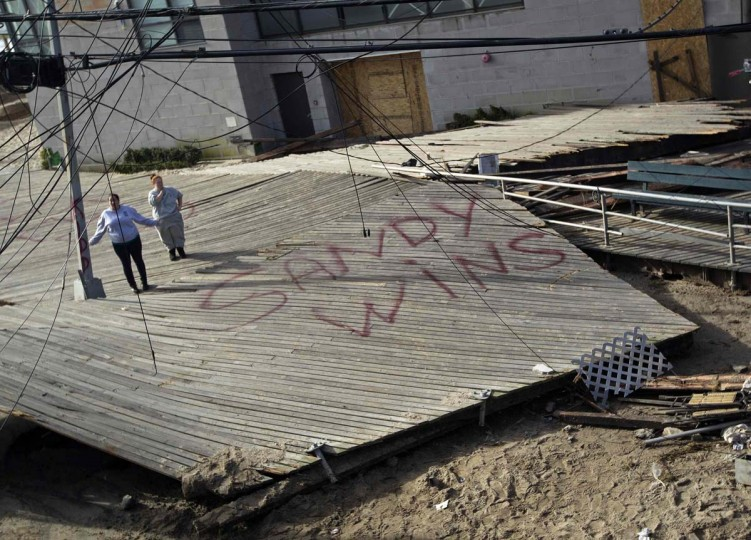 Women stand on a piece of the devastated Rockaway beach boardwalk that was blown onto Beach 91st street by Hurricane Sandy, in the Queens borough of New York. (Shannon Stapleton/Reuters photo)