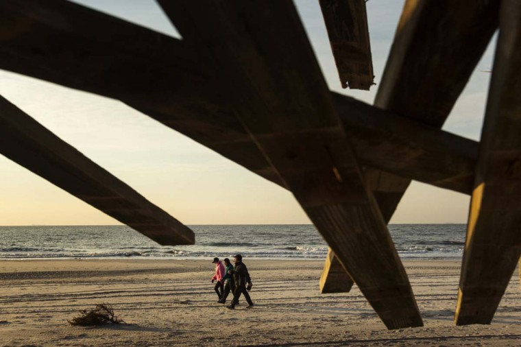 A group of people walk on the beach past sections of boardwalk damaged by the storm surge of superstorm Sandy in Long Beach, New York. (Lucas Jackson/Reuters photo)