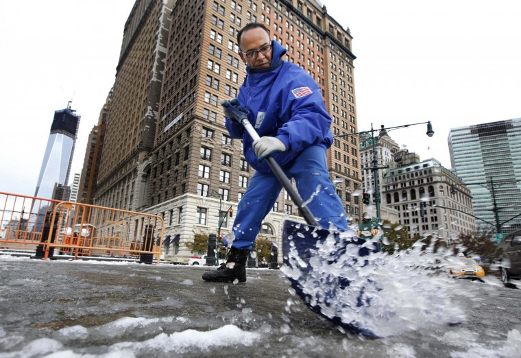 Gilber Hernandez clears snow from a sidewalk in New York's financial district, November 8, 2012. An unseasonably early nor'easter winter storm brought snow, rain and dangerous winds to the Northeast, plunging many residents of the most populous region of the country back into darkness just as they were recovering from Superstorm Sandy. (Brendan McDermid/Reuters photo)