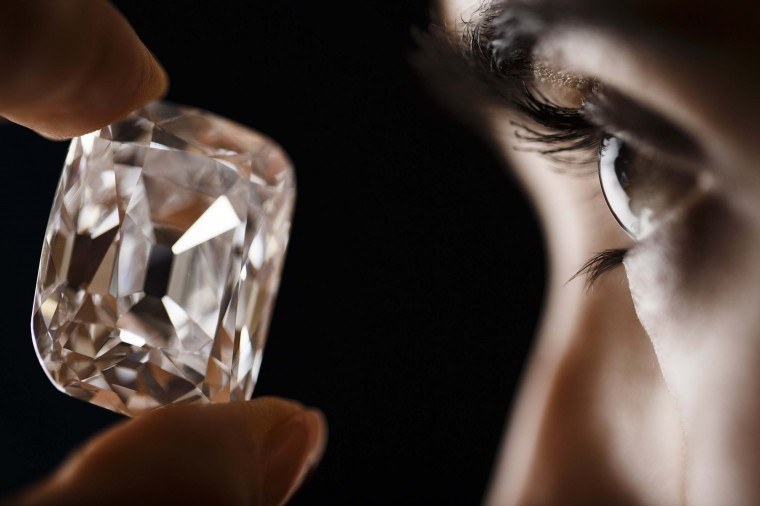 An employee poses with the Archduke Joseph diamond during an auction preview at Christie's in Geneva November 8, 2012. The 76 carat diamond is expected to fetch between 15 million and 20 million US dollars as it auctions in Geneva on November 13th. (Valentin Flauraud/Reuters photo)