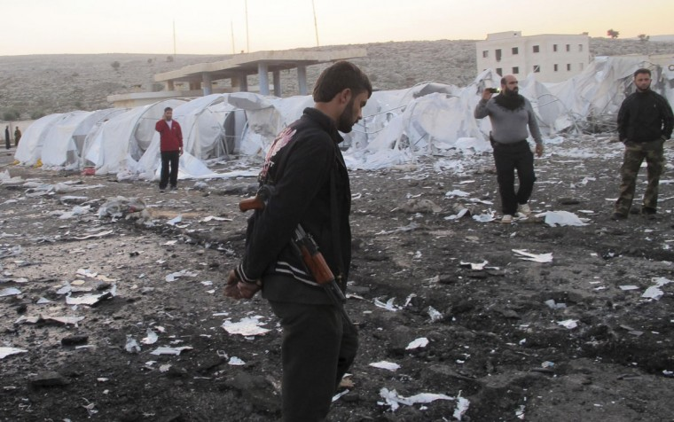 Free Syrian Army (FSA) fighters inspect the damage at an unfinished refugee camp that the FSA says was destroyed by Syrian regime air strikes in Bab Al-Hawa, near the Syria-Turkey border, November 26, 2012. (Abdalghne Karoof/Reuters)