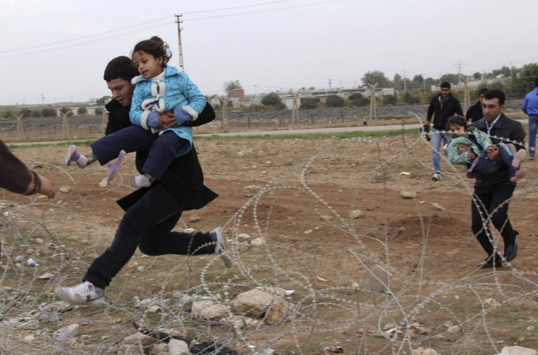 Syrians jump over barbed wire as they flee from the Syrian town of Ras al-Ain to the Turkish border town of Ceylanpinar, Sanliurfa province. Around 9,000 Syrian refugees fled into Turkey in the past 24 hours, the U.N. refugee agency said on Friday, and Turkish state media said 26 defecting Syrian army officers had also arrived. More than 120,000 registered Syrian refugees are now sheltering in Turkish camps. Tens of thousands of unregistered Syrians are also living in Turkish border towns and villages. (Stringer/Reuters)