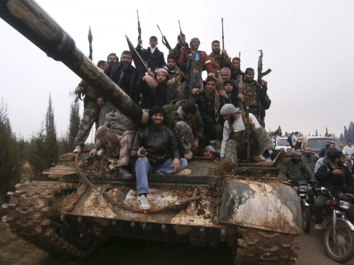 Free Syrian Army fighters pose on a tank, which they say was captured from the Syrian army loyal to President Bashar al-Assad, after clashes in Qasseer, near Homs November 19, 2012. (Shaam News Network/Handout/Reuters)