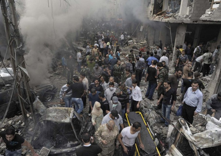 A crowd gathers in front of a building and car damaged after a bomb explosion in the Mezzeh 86 area in Damascus, in this handout photograph released by Syria's national news agency SANA, November 5, 2012. A bomb attack in a western district of Damascus killed 11 people and wounded dozens more, including children, on Monday, Syrian state media and an activist group reported. (Sana/Reuters)