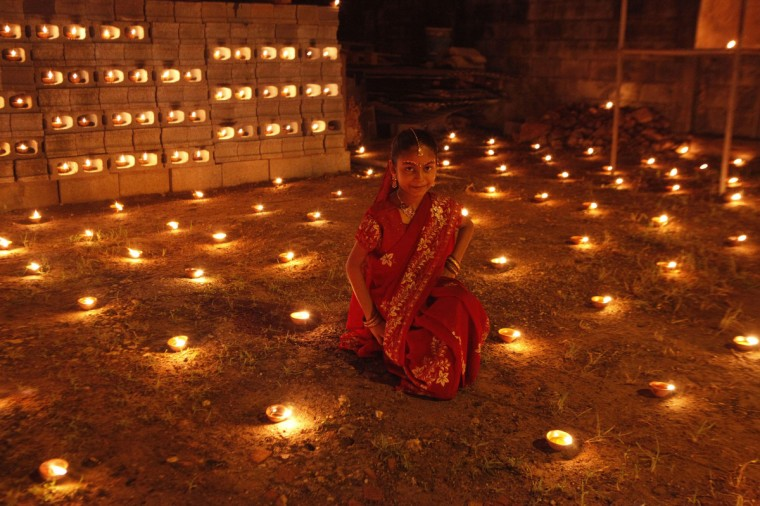 A girl sits among diyas, or oil lamps, in her yard during Diwali celebrations in Felicity, central Trinidad November 13, 2012. Hindus decorate their homes and places of worship with lamps or candles as a symbol of the victory of good over evil during Diwali, the festival of light. (Andrea De Silva/Reuters)