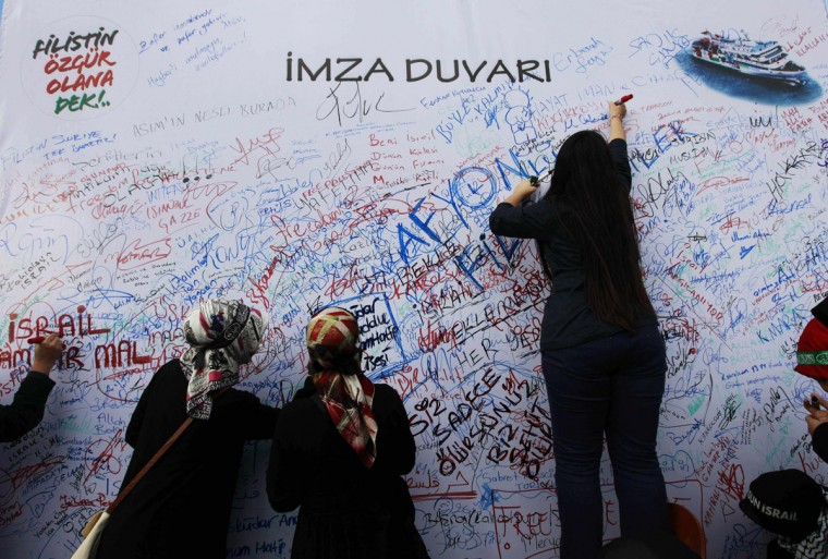 Protesters sign on a signature wall during a protest in front of a courthouse in Istanbul. Hundreds of protesters chanting 'Murderer Israel!' gathered outside an Istanbul court on Tuesday at the start of a trial of a group of former Israeli military commanders charged over the 2010 killing of nine Turks aboard a Gaza-bound aid ship. (Osman Orsal/Reuters)