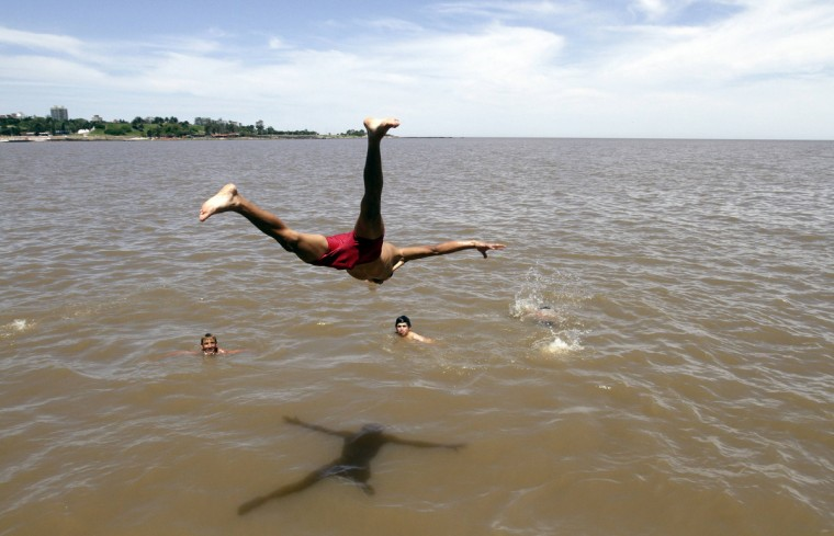 Youths dive into the river Plate from Montevideo's waterfront to cool off during a heat wave. Temperatures could reach 36 centigrade (96 Fahrenheit) in some areas of the country on today, according to the Uruguayan meteorological institute. (Andres Stapff/Reuters)