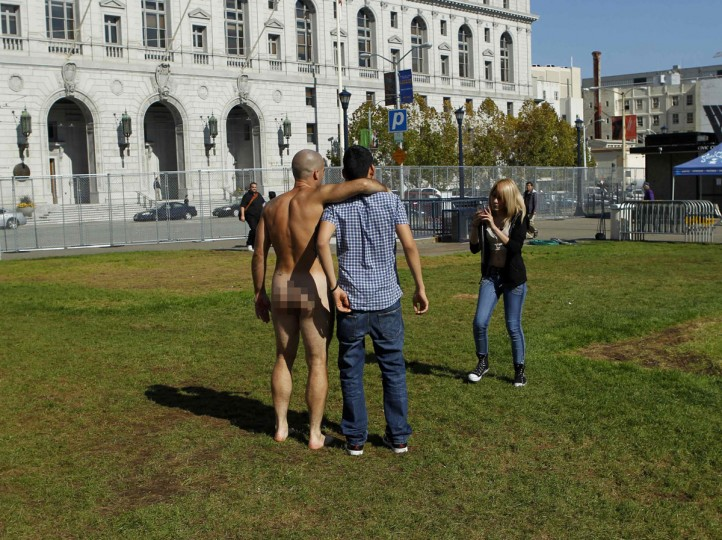 A dressed man poses for a picture with a nude man at Civic Center Plaza in San Francisco, California October 30, 2012. (Robert Galbraith/Reuters)