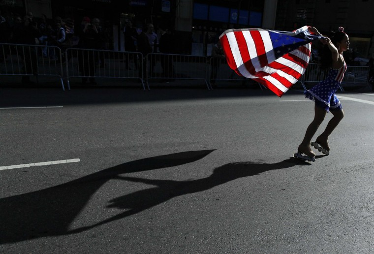A woman on roller skates holds an American Flag as she goes up 5th Avenue during the Veterans Day Parade in New York November 11, 2012. (Carlo Allegri/Reuters)