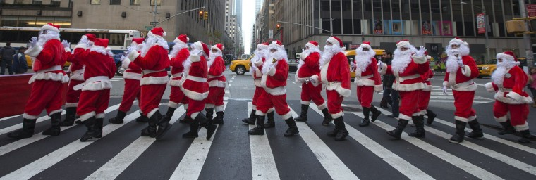 Some dozens of Santas ring their bells while marching through Midtown Manhattan during the Volunteers of America's 110th Annual Sidewalk Santa Parade in New York. (Adrees Latif/Reuters)