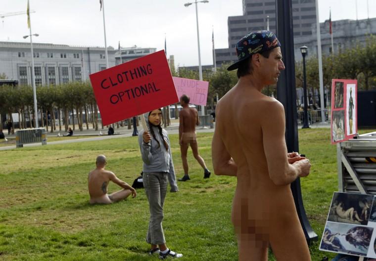 Inti Gonzalez, 11, carries a sign near nude men at Civic Center Plaza in San Francisco, California October 30, 2012. (Robert Galbraith/Reuters)