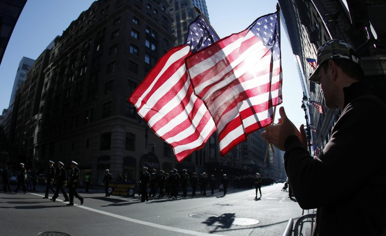 A man holds up American flags during the Veterans Day Parade in New York November 11, 2012. (Carlo Allegri/Reuters)