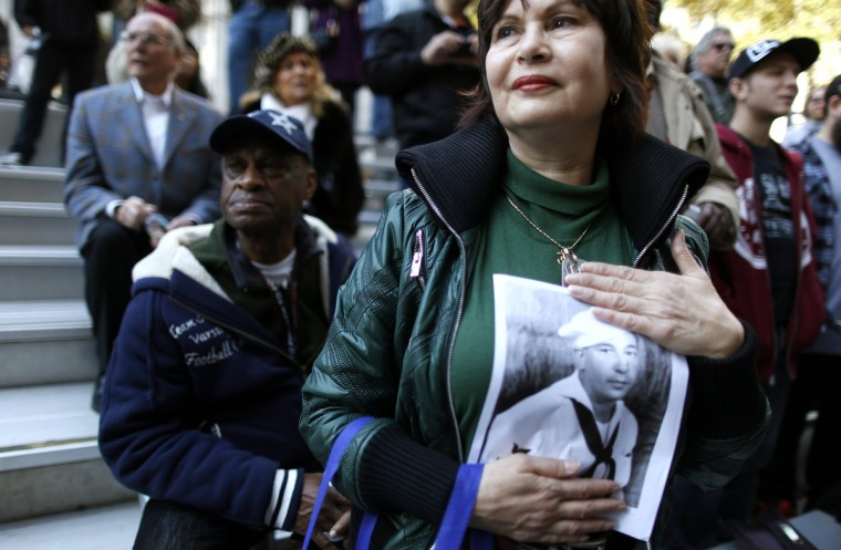 Carol Romeo holds up a photo of her father, Jack Romeo, a World War II veteran during the Veterans Day Parade in New York November 11, 2012. (Carlo Allegri/Reuters)