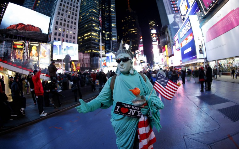 A man dressed as the Statue of Liberty watches TV screens in Times Square giving U.S presidential election results in New York November 6, 2012. (Carlo Allegri/Reuters)
