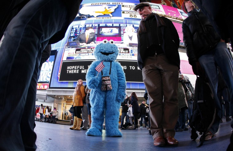 A man dressed as the character Cookie Monster watches TV screens in Times Square giving U.S presidential election results in New York November 6, 2012. (Carlo Allegri/Reuters)