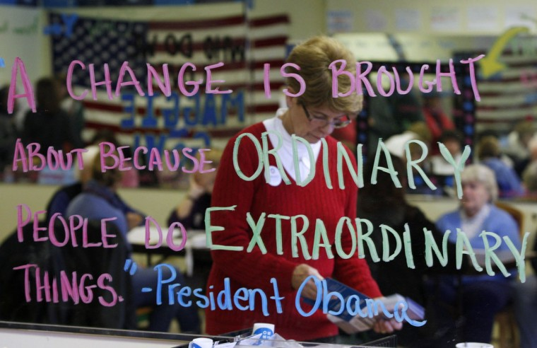 A volunteer for U.S. President Barack Obama is reflected in a mirror that has a quote written on it that is attributed to President Obama at the Obama for America New Hampshire Office in Derry, N.H. (Jessica Rinaldi/Reuters)