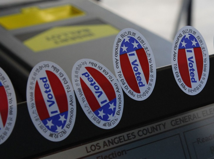 "Stickers stating ""I Voted"" in several languages are affixed to a ballot intake machine in the garage of Tom and Carol Marshall, which was made into a polling location in Los Angeles, Calif. The stickers were handed to voters as they returned their ballots. (Fred Prouser/Reuters)"