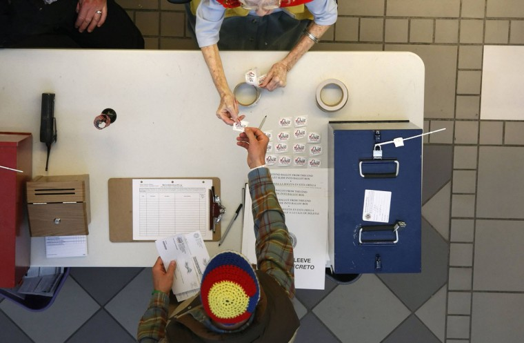 "A voter gets an ""I Voted"" sticker from Denver election worker Constance Rolon at the Denver Elections Division headquarters in downtown Denver during early voting. (Rick Wilking/Reuters)"