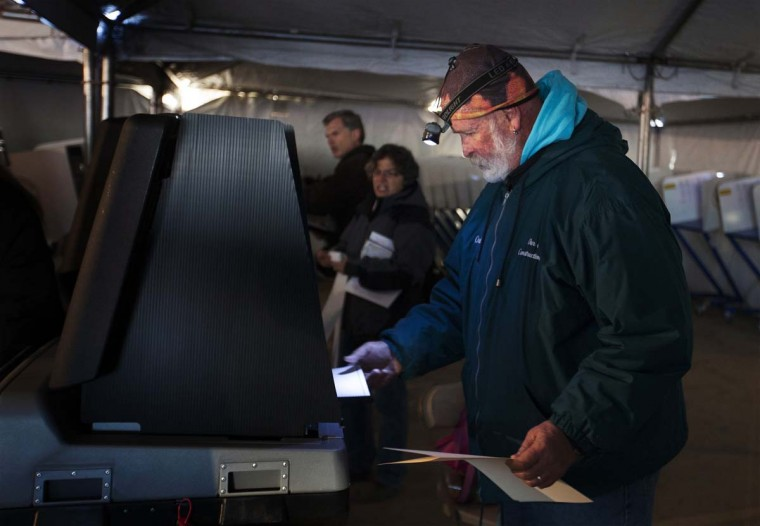 NY: A man uses a headlamp to see as he scans his vote in a polling site built to service residents of the Queens borough neighborhoods of Breezy Point and the Rockaways whose original site was damaged during hurricane Sandy, during the U.S. presidential election in New York, November 6, 2012. (Lucas Jackson/Reuters)